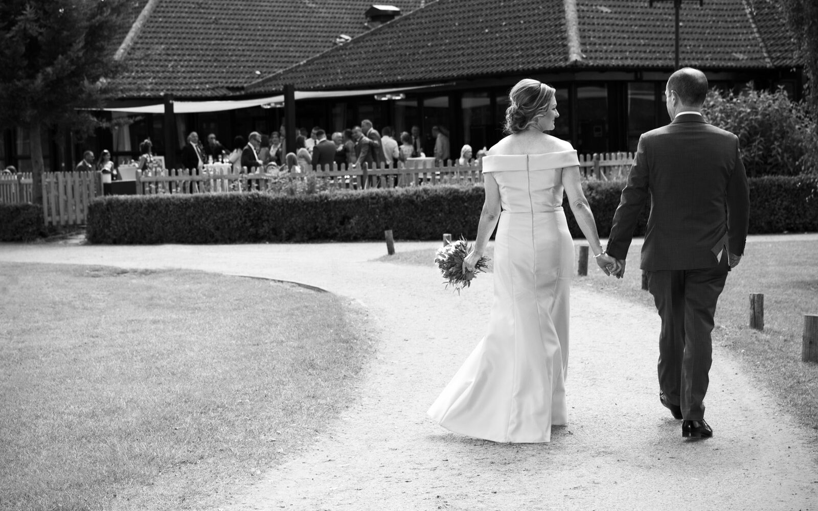 bride and groom taking a stroll around the grounds at their Weald of Kent wedding in Headcorn