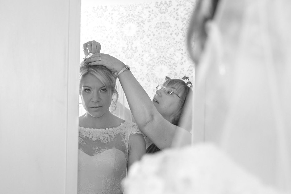 bride's mother making finishing touches to veil before wedding ceremony at Brooks Guesthouse in Bristol