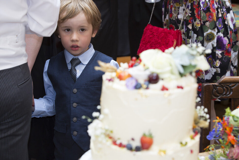 little boy looking lovingly at wedding cake at The Cosy Club in Bristol
