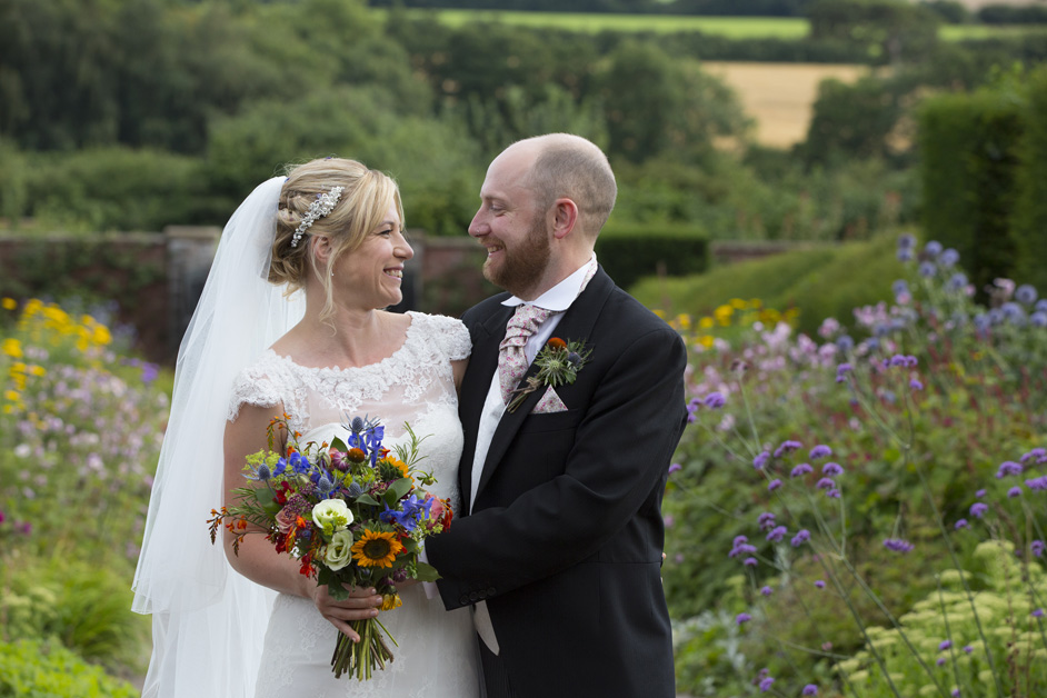 bride and groom in an embrace at their Bristol wedding reception enjoying the grounds at The Ethicurean