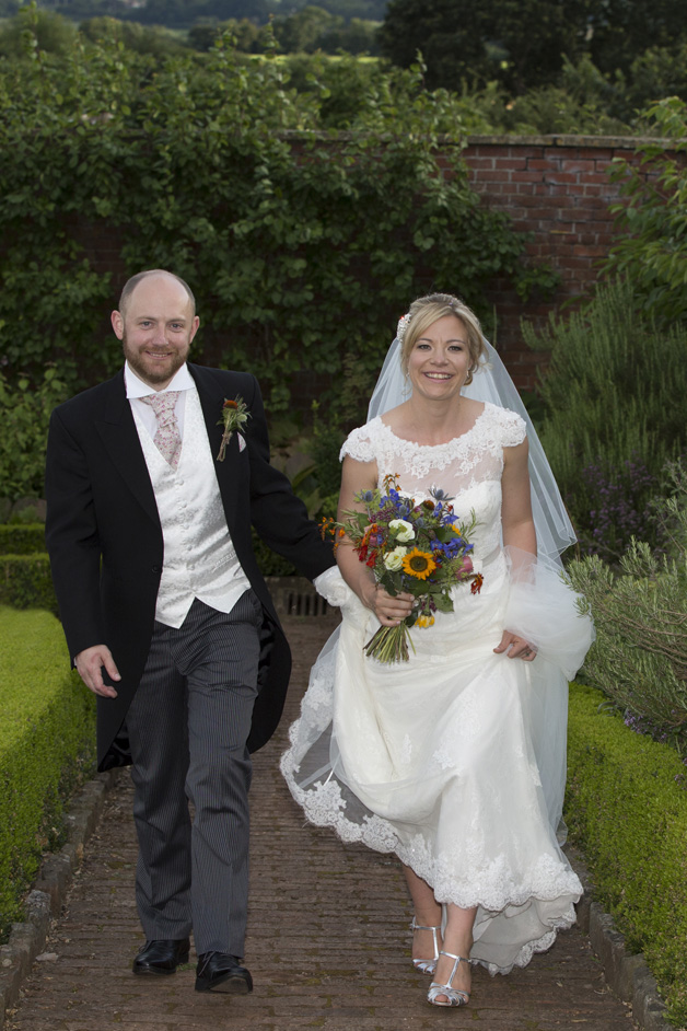 bride and groom walking through the grounds at their Bristol wedding reception at the Ethicurean