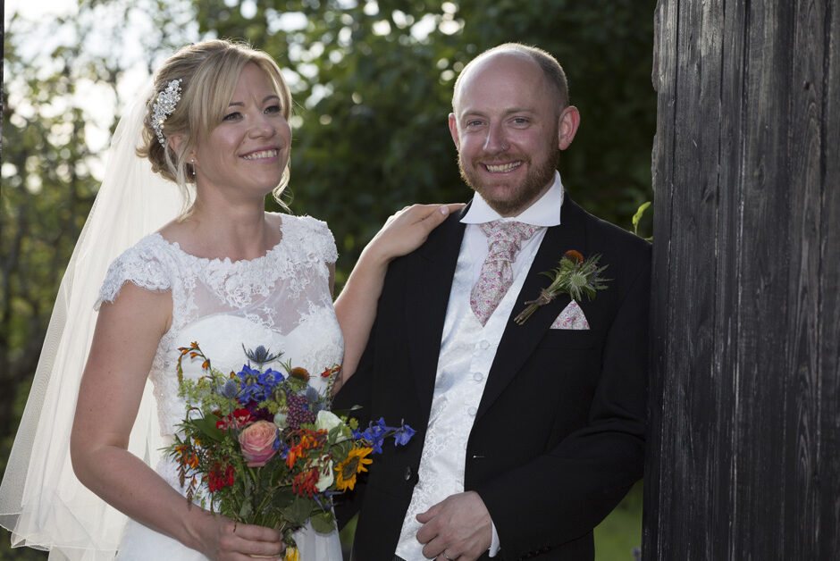 bride and groom standing against gate at their Bristol wedding reception at The Ethicurean