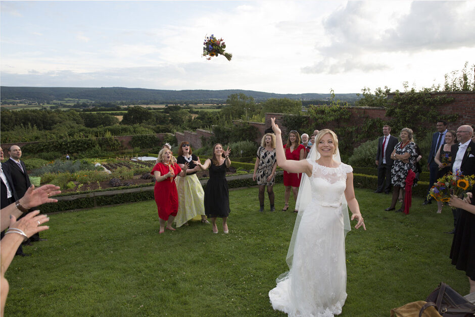 bride throwing the bouquet to three ladies at The Ethicurean in Bristol