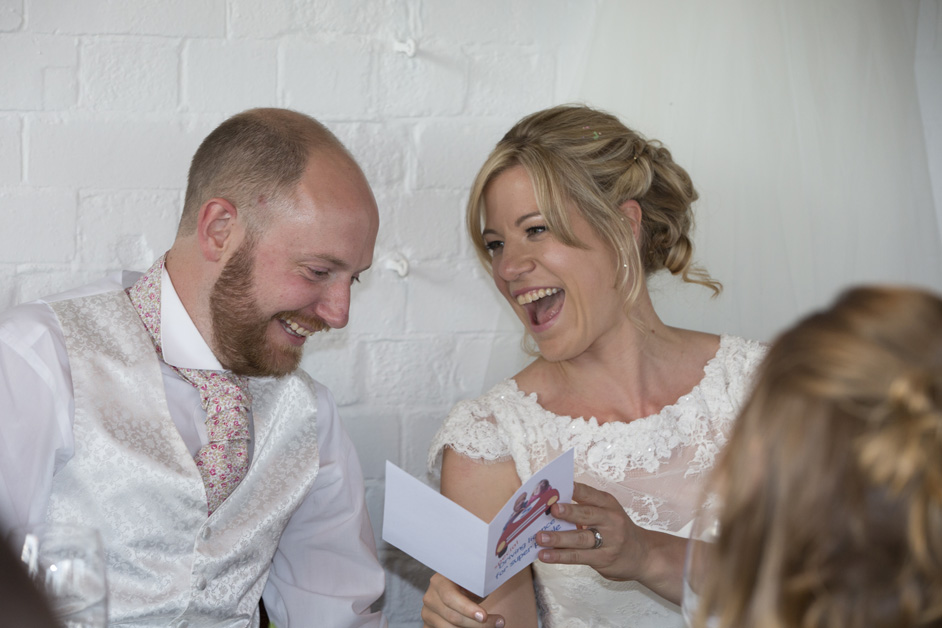 bride and groom laughing over a card received during the wedding speeches at The Ethicurean in Bristol