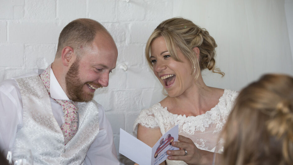 bride and groom laughing at a card given to them during speeches at their Bristol wedding