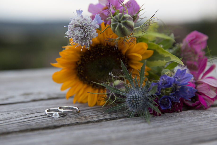 bride's engagement and wedding ring on country bench with sunflower bouquet at Bristol wedding reception at The Ethicurean