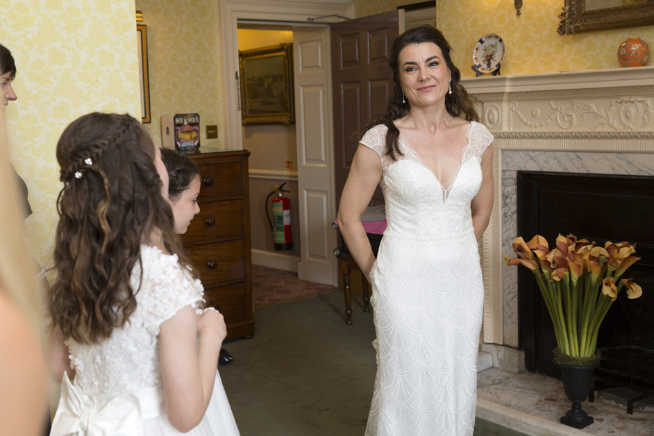 bride entering the bridal suite at The Shelleys in Lewes showing bridesmaids her dress for the first time