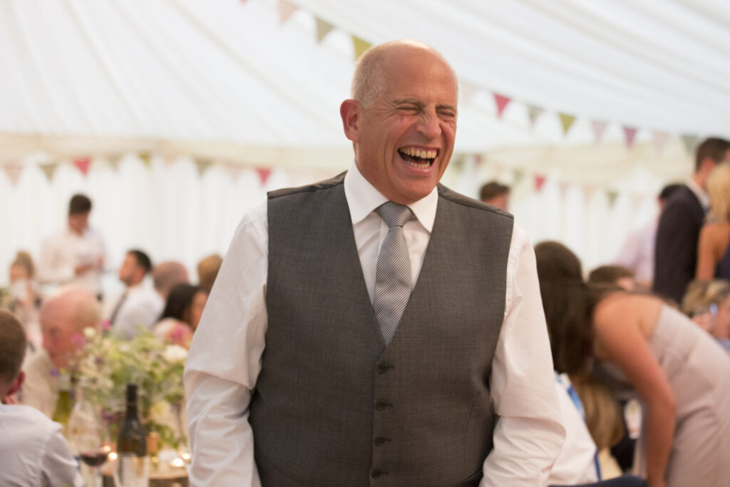 father of the groom laughing his head off in marquee at Smarden wedding in Kent