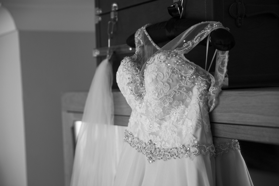 bride's dress hanging on a suitcase at Wotton House in Dorking, Surrey