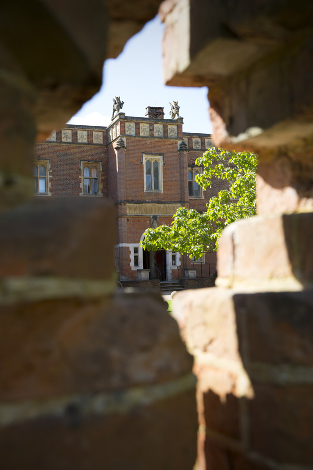 view of the front of Wotton House in Dorking, Surrey through a hole in a brick wall