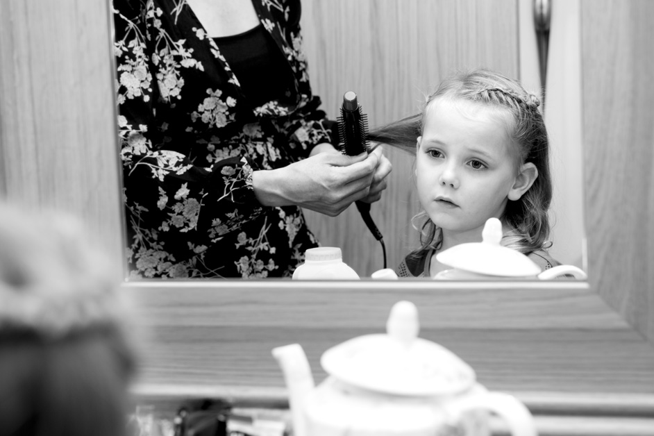 flower girl looking at her hair in the mirror at Wotton House wedding in Dorking, Surrey