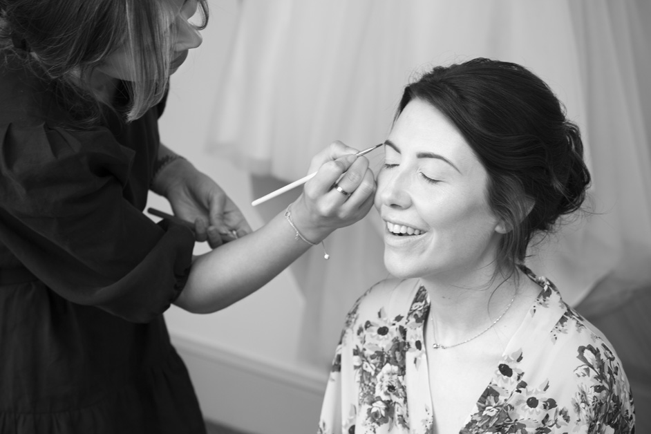 bride getting ready having her eyebrows lined at Wotton House wedding in Dorking, Surrey