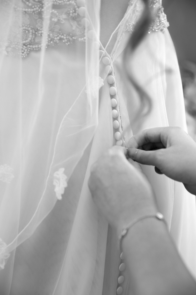 bride's dress being buttoned up at Wotton House wedding in Dorking, Surrey