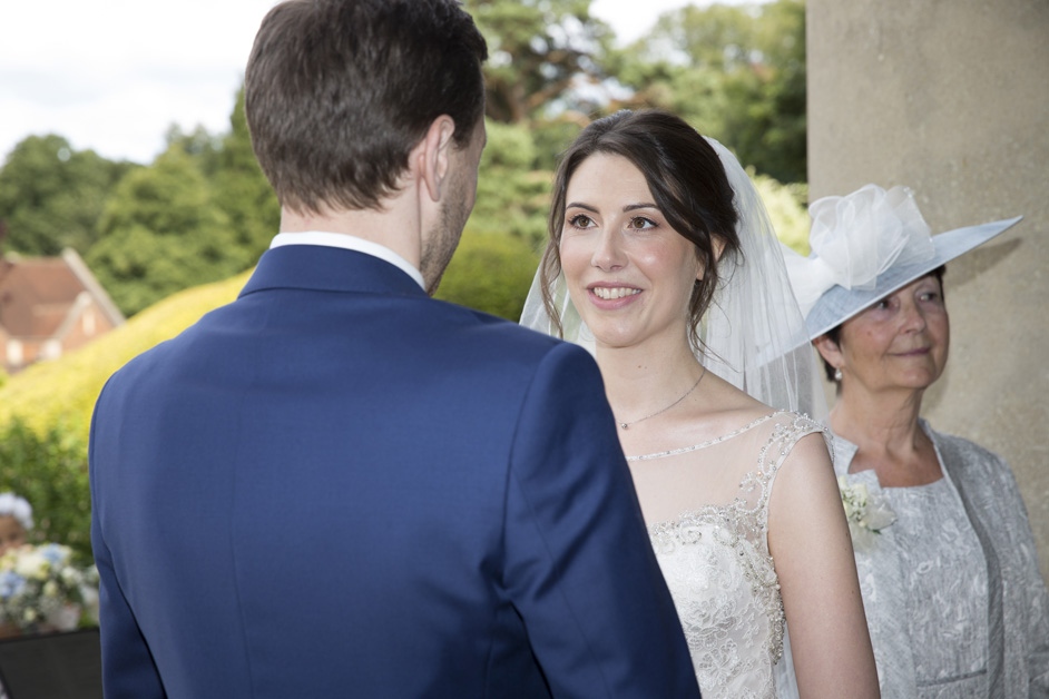 bride looking lovingly at groom during vows at outside ceremony at Wotton House wedding in Dorking, Surrey