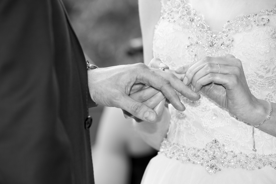 close-up of bride and groom's hands exchanging the rings in outdoor ceremony at Wotton House wedding in Dorking, Surrey