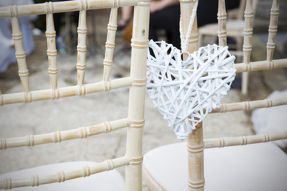 close-up of white wooden woven heart hanging over chair at outside ceremony at Wotton House wedding in Dorking, Surrey