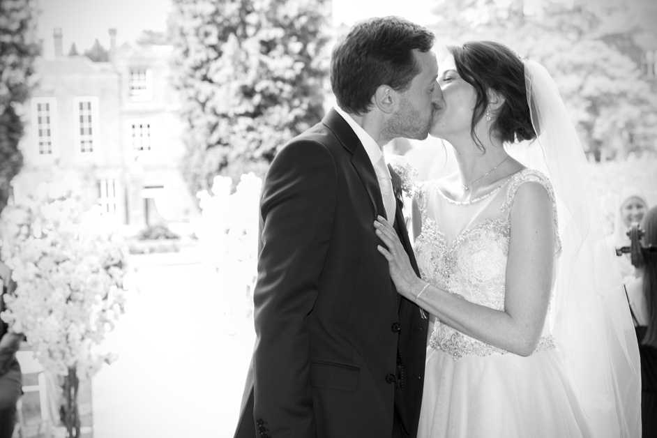 bride and groom sharing romantic kiss at outdoor ceremony at Wotton House wedding in Dorking, Surrey