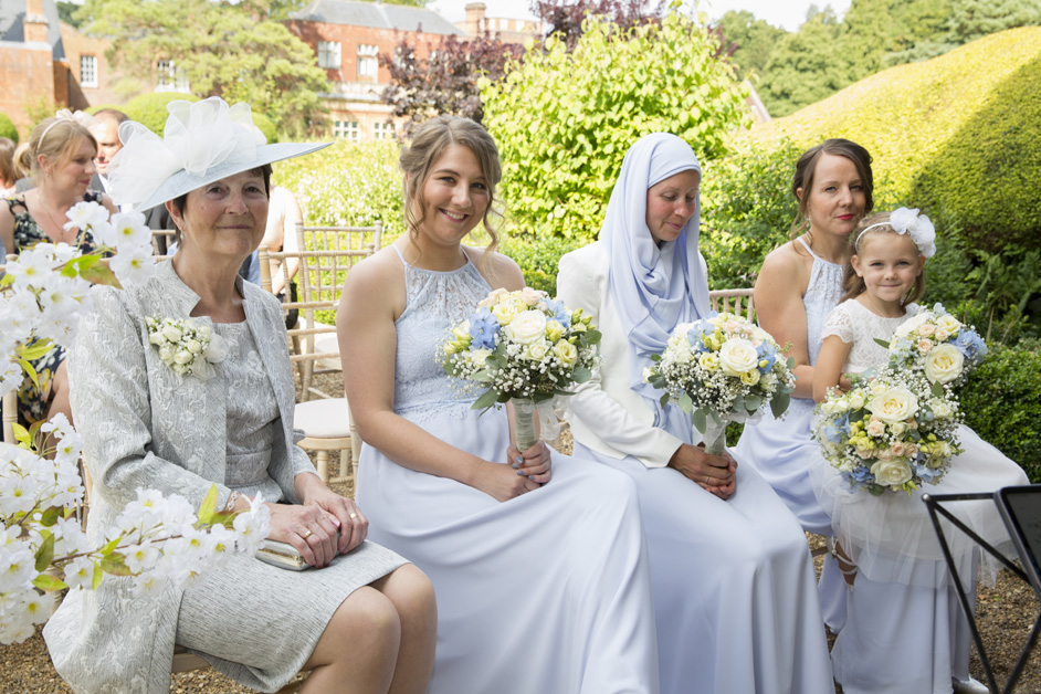 mother of the bride and bridesmaid sitting at outdoor ceremony at Wotton House in Dorking, Surrey