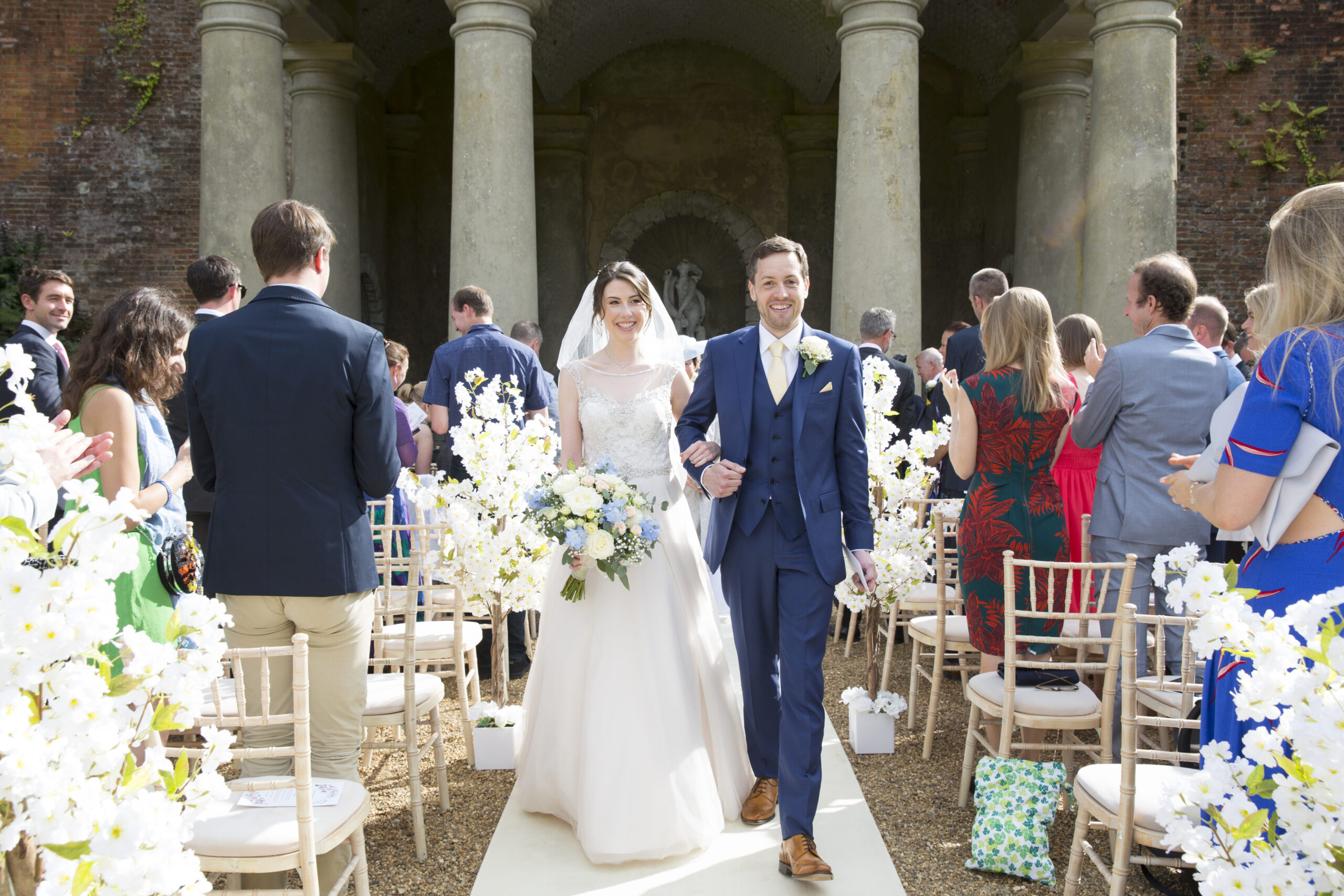 bride and groom walking up the aisle after their outdoor ceremony at Wotton House in Dorking, Surrey