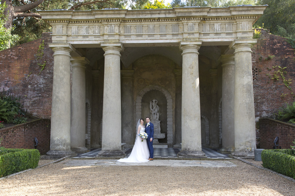 bride and groom posing outside the mock roman temple at Wotton House wedding in Dorking, Surrey