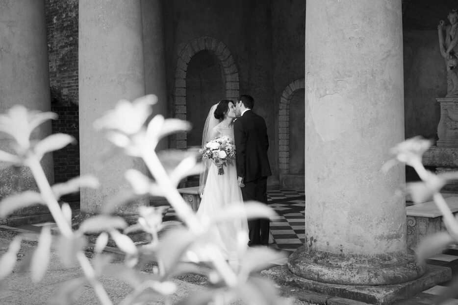 bride and groom kissing under the temple at Wotton House wedding in Dorking, Surrey