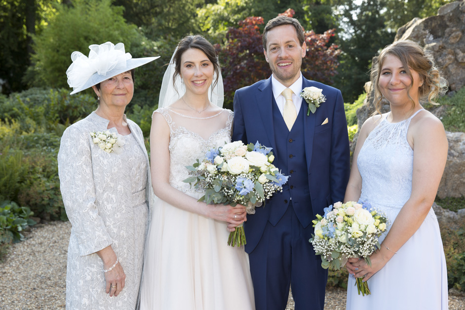 bride and groom with mother of the bride and sister bridesmaid at Wotton House wedding in Dorking, Surrey