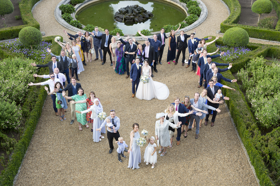 bride and groom with all their guests making heart shape at Wotton House wedding in Dorking, Surrey