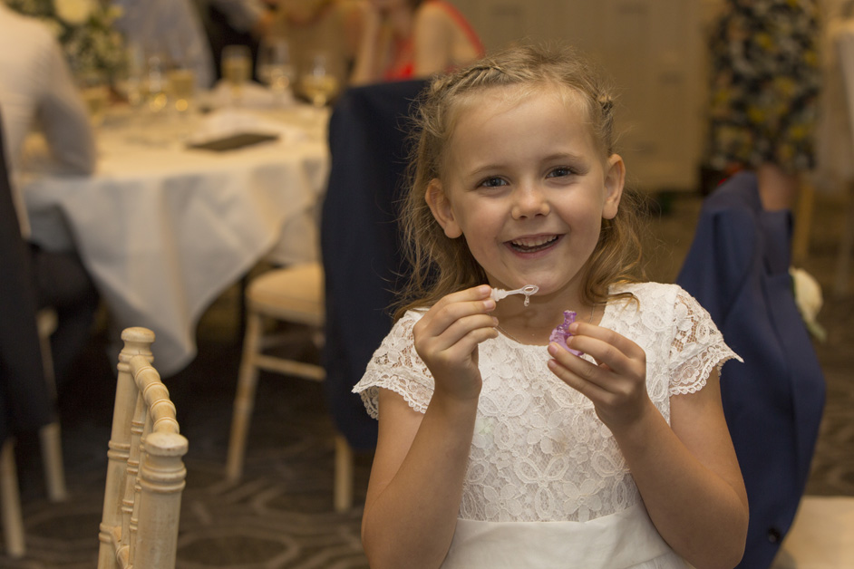 flower girl blowing bubbles at wedding reception at Wotton House in Dorking, Surrey
