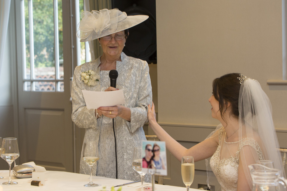 bride supporting mother during speeches at Wotton House wedding in Dorking, Surrey