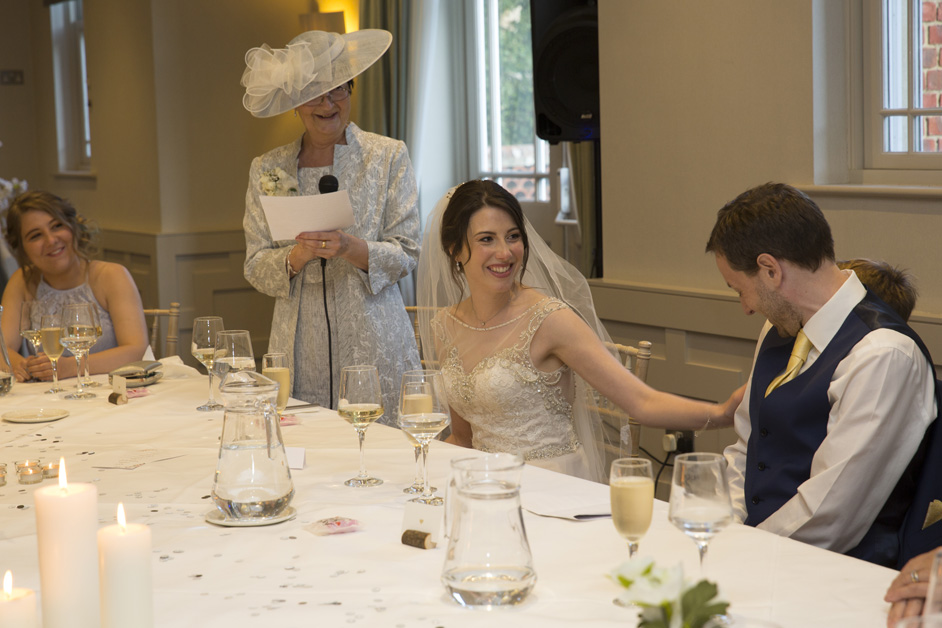 bride placing a loving arm on groom during her mother's speech at Wotton House wedding in Dorking, Surrey