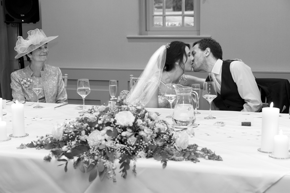 bride and groom having a romantic kiss during wedding speeches at Wotton House, Surrey