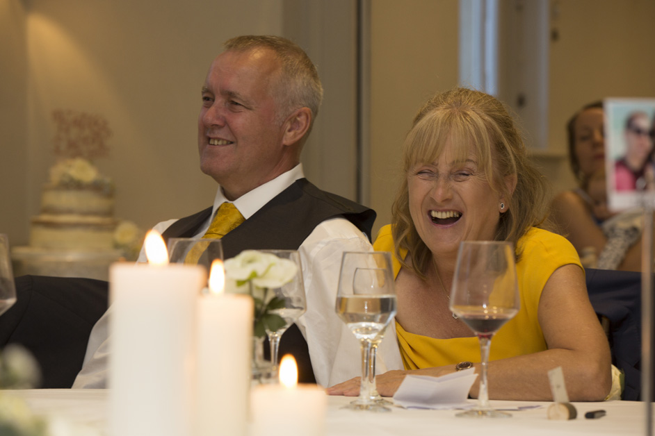 groom's parents laughing during wedding speeches at Wotton House in Dorking, Surrey