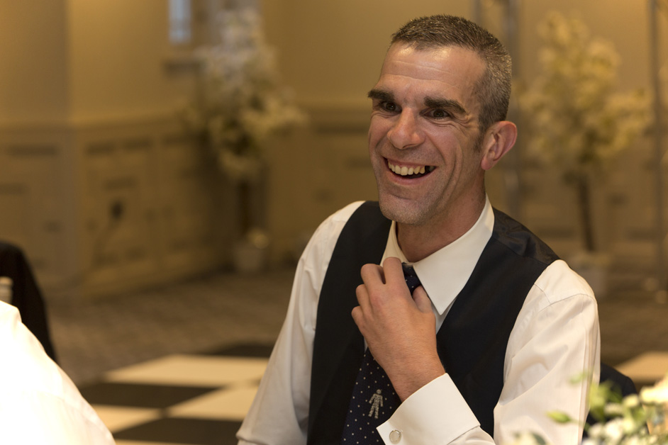 male guest laughing during wedding speeches at Wotton House in Dorking, Surrey