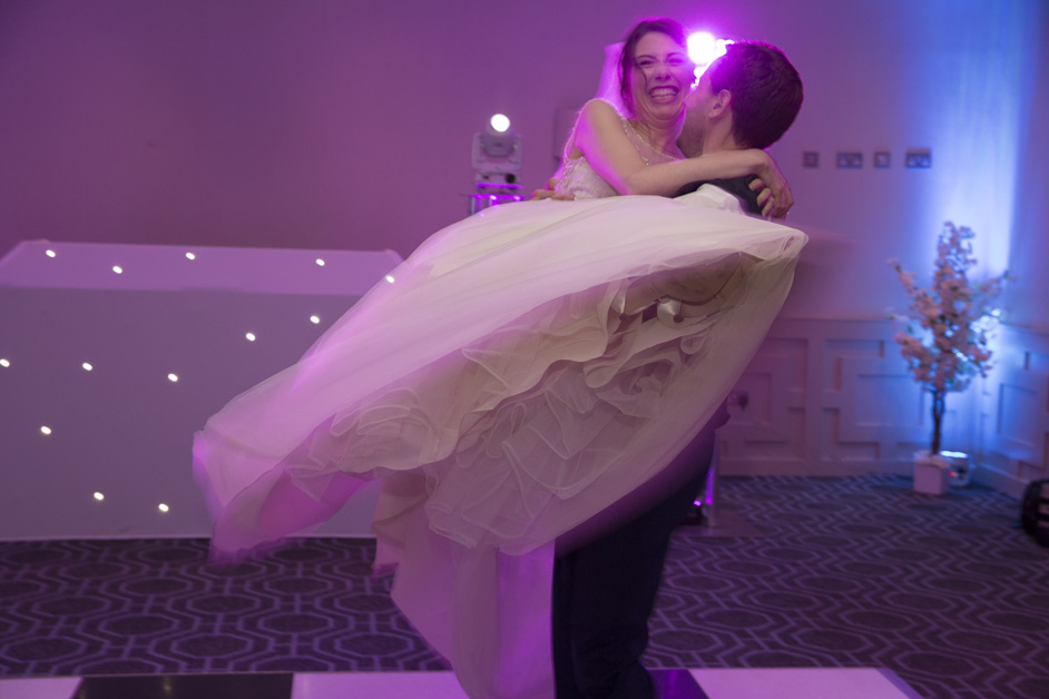 bride being picked up by groom in dance routine at Wotton House wedding in Dorking, Surrey
