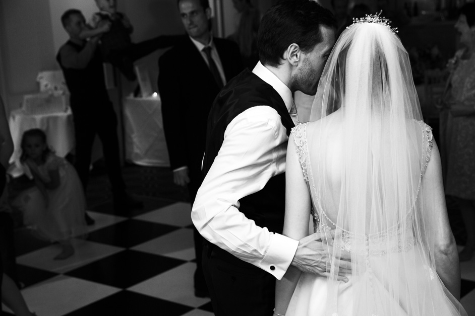 groom lovingly putting arm around bride's back on dance floor at Wotton House in Dorking, Surrey