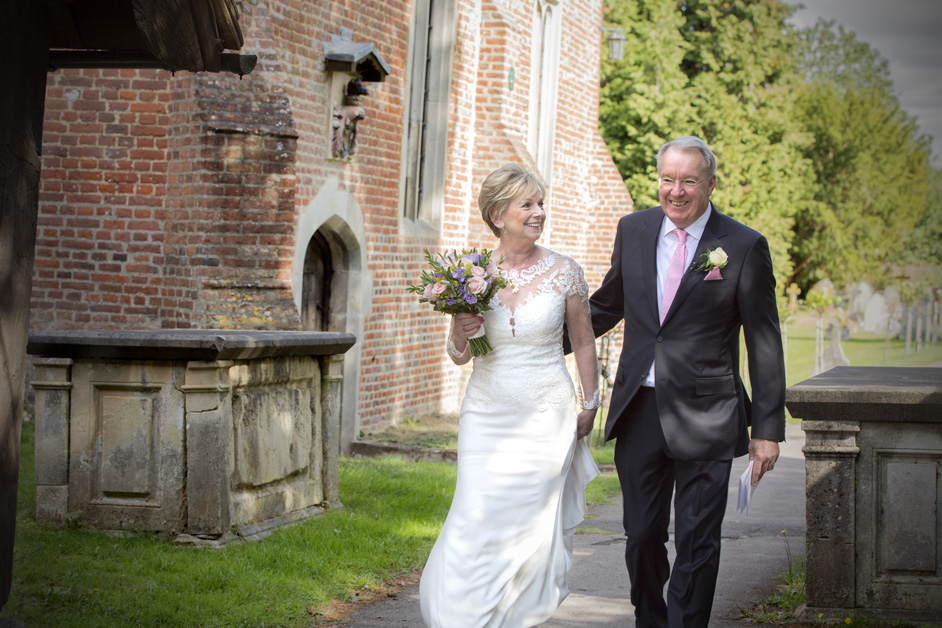 bride and groom walking into entrance of Stoke Poges Church for wedding ceremony in Reading