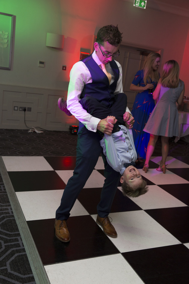 groom's brother holding little boy upside down on dance floor at Wotton House wedding in Dorking, Surrey