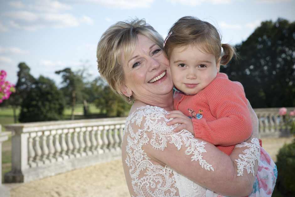 smiling bride posing with toddler grandchild at Stoke Park wedding reception in Reading