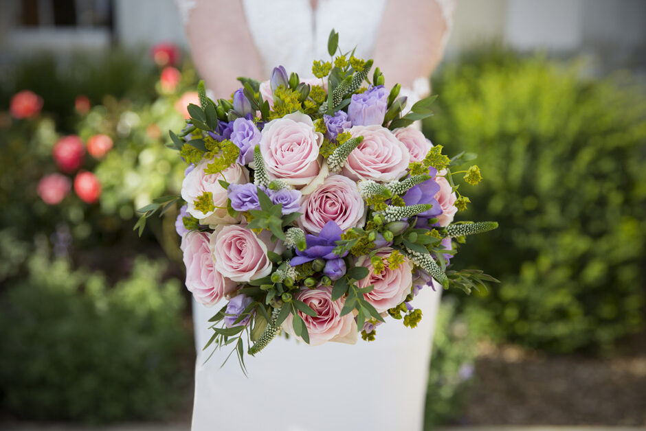 bride's holding out pink rose wedding bouquet at Stoke Park wedding reception in Reading