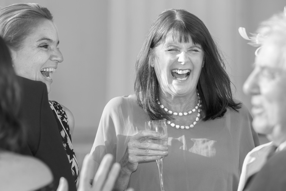 female wedding glass holding champagne glass laughing uncontrollably at Stoke Park wedding reception in Reading