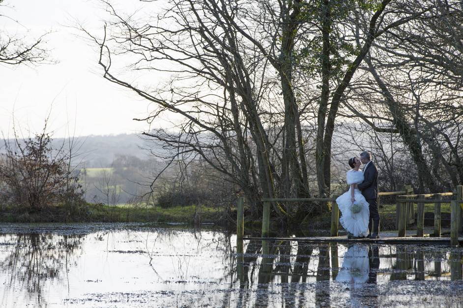 bride and groom sharing a romantic moment by the lake at Swallows Oast, Tunbridge Wells