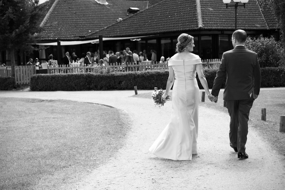bride and groom walk back towards their wedding guests at The Weald of Kent in Headcorn