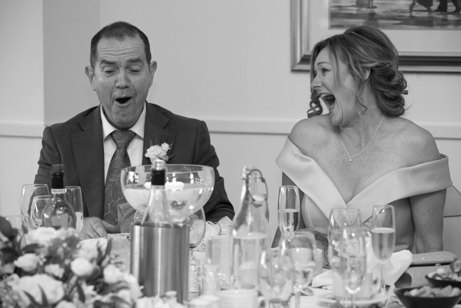 groom looking shocked and bride laughing during wedding speeches at Weald of Kent in Headcorn