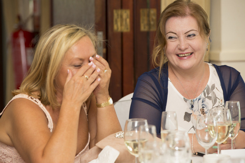 female wedding guests laughing during speeches at The Weald of Kent in Headcorn