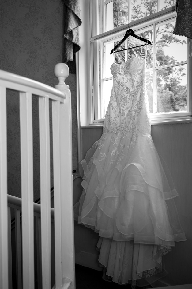 wedding dress handing on large window by hallway staircase at The Old Rectory at Hartwell House in Buckinghamshire