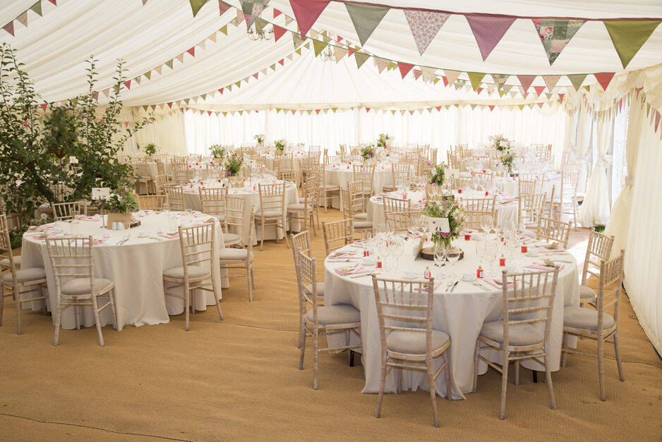 marquee with decorative bunting and tables at Smarden village wedding in Kent