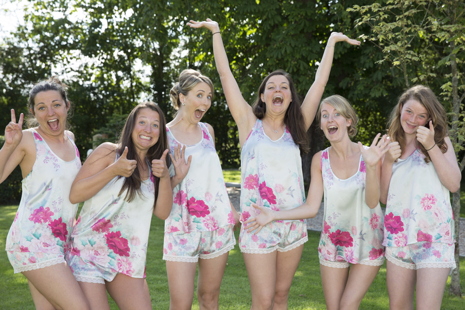 bridesmaids making funny silly poses in matching silk pyjamas at Smarden village home in Kent