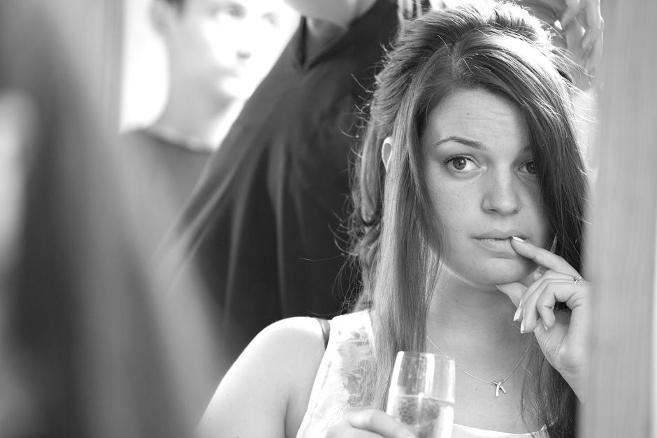 bride looking in mirror unsure about her hair during bridal prep at Smarden village home in Kent