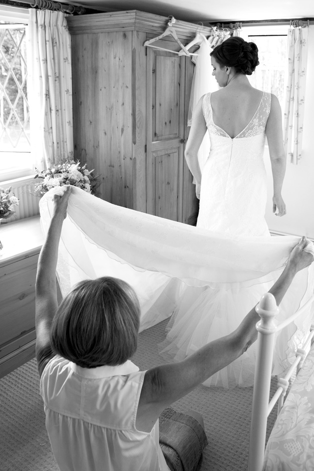 bride's mum helping bride with back of dress at Smarden village home in Kent