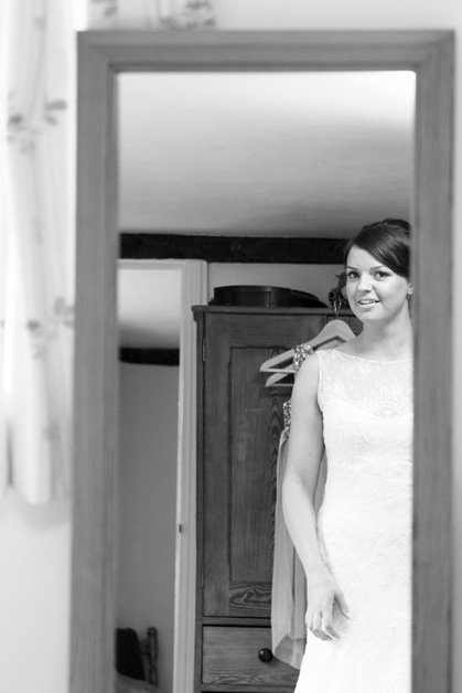 bride looking in mirror at her dress during bridal prep at Smarden village home in Kent